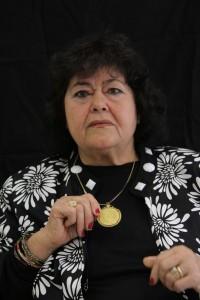 """גיטה סמיה עונדת תכשיט שקבלה מאמה. מתוך התערוכה """"הזהב של אמא"""". צילום: חן לאופולד."""