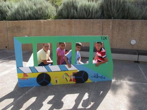 """משתתפי התכנית """"לגשר על הפער"""" מציגים את פרויקט סיום שנת 2013: אוטובוס מצויר מבפנים ומבחוץ המשקף את עולמם של הילדים. צילום: בני מאור"""