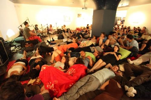 """הרדמה: קונצרט לילי מדיטטיבי בשכיבה בתערוכה """"לילה טוב"""" באגף הנוער הוזמנו המבקרים לחלוץ נעליים, להשתרע על המזרנים, להתכסות ולהאזין ליצירה מקורית שהיא בה בעת מנחמת ואפלה. נגנים: נועם ענבר - שירה, אקורדיון, צ'מבלו; אדם שפלן - גיטרה חשמלית; אריאל ערמוני - כלי הקשה; יוני סילבר - כינור, קלרינט, בס. צילום: ברק אהרון"""