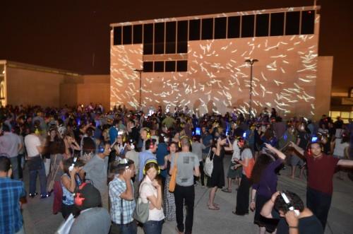 """מסיבת אוזניות בשקט מוחלט האמן גיא יצחקי מרקיד את קיר המוזיאון בעבודת וידאו שיצר במיוחד ל""""נקודת מגע"""" בהשראת עבודת הנקודות המונומנטלית """"L-Leucine-15-N"""" מאת דמיין הרסט שתלויה באולם העליון, ובהתייחסות לאדריכלות של הקיר עצמו. צילום: יפים ברבלט"""