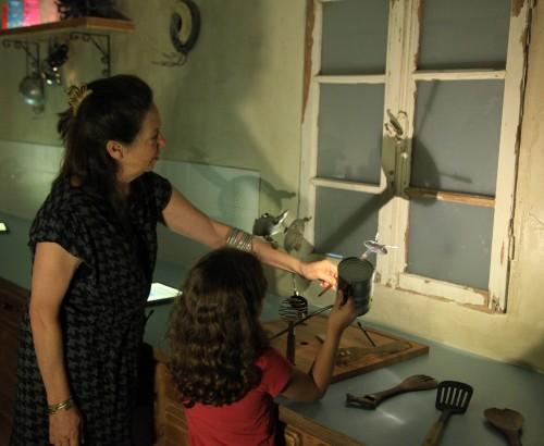 מבוגרים וילדים יוצרים תיאטרון צלליות עם כלי המטבח בתערוכה משחקי אור וצל. צילום: ששון תירם
