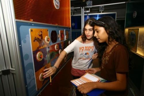 """נערות בתערוכת """"מבוך השלום"""" שומעות מילים ב-16 שפות ומנסות לגלות את משמעותן לפי האינטונציה. צילום: מוזיאון המדע ע""""ש בלומפילד ירושלים"""