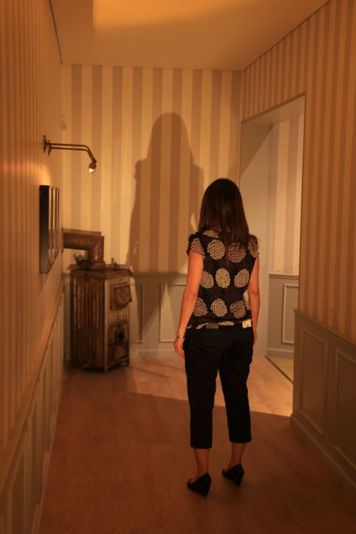 """מבקרת עוקבת אחרי שינוי גודל הצל בזמן הליכה במסדרון בתערוכה """"משחקי אור וצל"""". צילום: ששון תירם"""