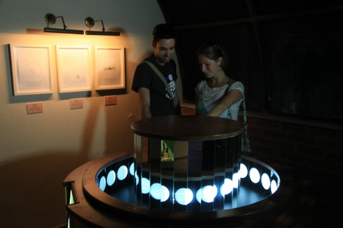 """מבקרים צופים בשינוי גודל הצל של הירח במוצג הפרקסינוסקופ בתערוכה """"משחקי אור וצל"""". צילום: ששון תירם"""
