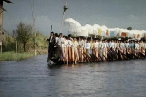 """דפנה שלום, """"דרך בורמה"""",2008, וידיאו,21:00דקות. לופ טקס המתקיים בכל שנה בבורמה ובו גוש מלוכד של כמאה גברים משיט סירה צרה וארוכה על קו המים. שם העבודה משמר את האסוציאציה הישראלית המלחמתית ומתעמת איתה. קבוצת הגברים מסורה לפעולה רוחנית ולא מלחמתית. הדקות המעטות המסומנות על המים מעוררות תחושות רוחניות מצד אחד ואסוציאציות הישרדותיות מצד שני. """"מַאֲמָץ מְאֻחָד, עַקְשָׁנִי וָעֵר/ שֶׁל אֶלֶף זְרוֹעוֹת. הַאֻמְנָם יִבָּצֵר לָגֹל/ אֶת הָאֶבֶן מִפִּי הַבְּאֵר?"""" (""""כאן על פני האדמה"""", רחל, תל-אביב, תרפ""""ז)"""
