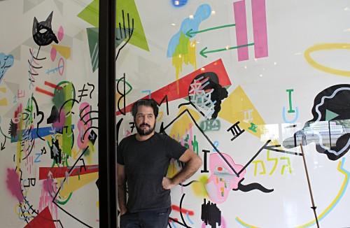 שרון פדידה וקיר האמן בקפה. צילום: דן אוריאלי